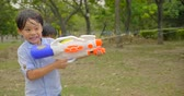 Happy children playing with water guns on summer Wideo
