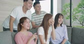 Group of young people watching TV together at home Stockvideo