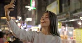 telemóvel : happy young asian woman using smart phone in Night Market