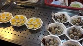curry : Quail Eggs.  A display of both cooked and fresh Quail eggs in an Asian market.