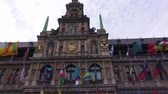 belga : The Town Hall - Antwerpen - Belgium.   Pan from top to bottom of the Town Hall in Antwerpen, Belgium. The front of the buiolding boasts several colouful flags blowing in a strong breeze.