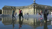 gironde : FRANCE, BORDEAUX - SEPTEMBER 20: People having fun in a mirror fountain in front of Place de la Bourse in Bordeaux, France. Time-lapse video Stock Footage