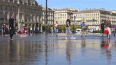 gironde : FRANCE, BORDEAUX - SEPTEMBER 20: People having fun in the mirror in the front of the Place de la Bourse in Bordeaux, France on September 20, 2015