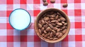 item : top view of almond in a bowl and milk on table
