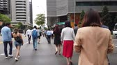 saamhorigheid : business people at early morning crossing street in Orchard Rd, Singapore.