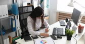 três quarto comprimento : businesswoman filling documents and working on laptop in modern office