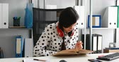 dokumenty : woman with red headphones on shoulders writting with pencil in notebook in modern office