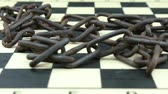 отставка : Old rusty chain on a chessboard Стоковые видеозаписи
