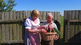 lawn : Old man holding a basket of ripe vegetables collected,and a woman examines them.