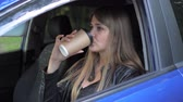 ninhada : Young Beautiful Woman Sitting In The Car And Drink Coffee