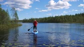 veslo : Man Floats On Lake On A Inflatable Boat Standing On Her, Rowing With Hands Oars