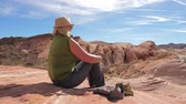 взял : Active Woman Tourist Sitting Resting On Red Rock And Admiring Views Of Canyon Стоковые видеозаписи
