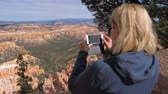 výhonky : Woman Tourist Standing On Lookout Point In Bryce Canyon And Photos To Smartphone Dostupné videozáznamy