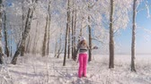 suéter : Woman Enjoying Winter Snow Outdoors Throwing Snow and Standing Under Snowfall