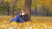 steadicam : Woman Sitting With His Back To Tree In Yellow Autumn Leaves, Talking Smartphone