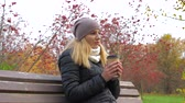 üvez ağacı : Woman Sitting On Bench Drinking Coffee In Autumn On A Background Of Red Rowan 4K