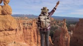 elevação : A Hiker Woman Raises Her Hand, Standing Over The Edge Of The Bryce Canyon