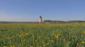 uzanmış : Pretty Woman In Dress Running In A Field With Yellow Flowers And Raising Arms