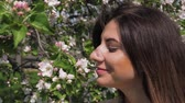 cheirando : Closeup Young Caucasian Woman Sniffs Flowers Of Blooming Apple Trees In Garden