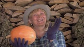 checks : Woman Farmer On The Background Of Folded Firewood Is Holding A Ripe Pumpkin