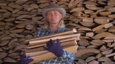 bundle of : Portrait Of A Woman In A Warehouse Holding An Armful Of Firewood