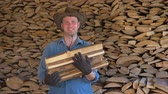 vaqueiro : Portrait Of A Man In A Cowboy Hat In A Warehouse Holding A Bunch Of Firewood
