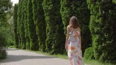 cipreste : A Woman In A Dress Coming Through A Neat Alley Of Decorative Tui On A Sunny Day