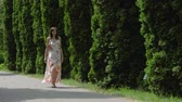 cipreste : Woman In A Dress Walking On Alley Of Decorative Cypress On A Sunny Summer Day