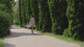 cipreste : Caucasian Attractive Woman In A Dress Running Down The Alley Of Decorative Trees Stock Footage