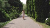 cipreste : Pretty Woman In A Dress Walking On Alley Of Decorative Trees On A Summer Day