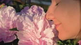 piwonie : Closeup Of Caucasian Woman Sniffing White Peonies And Enjoying The Smell