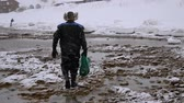 diving equipment : Fisherman Goes With A Full Grid Of Seafood Is On The Seashore In Winter Stock Footage