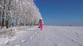 correção : Woman Running Away Into The Distance On A Snow Covered Field On Winter Fairy Day