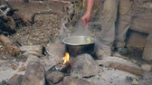 konvice : Hand Tourist Mixes The Pasta With A Spoon In The Pot On The Fire In A Camp Dostupné videozáznamy