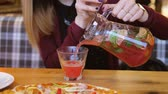 glass jugs : In Cafe At Table Close Up Woman Hands Pour The Juice From Decanter Into A Glass