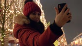 christmas market : Woman Taking Selfie On Smartphone Standing At Christmas Fair In The Evening Stock Footage