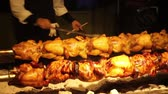 basting : Chickens on rotisserie barbecue spinning at restaurant with chef tending to them.