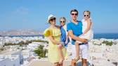santorin : Family vacation in Europe. Parents and kids background the old town in Mykonos island, Greece