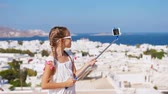 Киклады : Adorable little girl taking selfie photo background Mykonos town in Greece