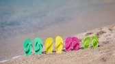тапочка : Family flip flops on beach in front of the sea