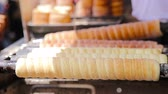 булыжник : Street food at Prague market outdoors. Process of making Traditional czech bakery products trdelnik.