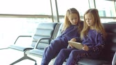 boarding pass : Little adorable girls in airport waiting for boarding and playing with laptop