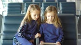 passaporte : Little adorable girls in airport waiting for boarding playing with laptop Stock Footage