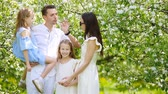 prole : Family of four in blooming garden on beautiful spring day