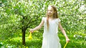 koku : Adorable little girl in blooming apple garden on beautiful spring day