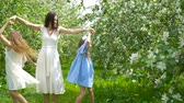prole : Adorable little girls with young mother in blooming garden on beautiful spring day