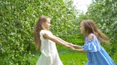 okładka : Adorable little girls in blooming apple tree garden on spring day