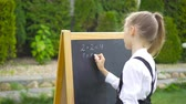 grader : Happy little schoolgirl with a chalkboard outdoor Stock Footage
