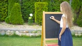 notas : Happy little schoolgirl with a chalkboard outdoor Vídeos
