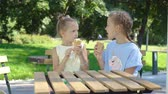 lody : Little girls eating ice-cream outdoors at summer in outdoor cafe
